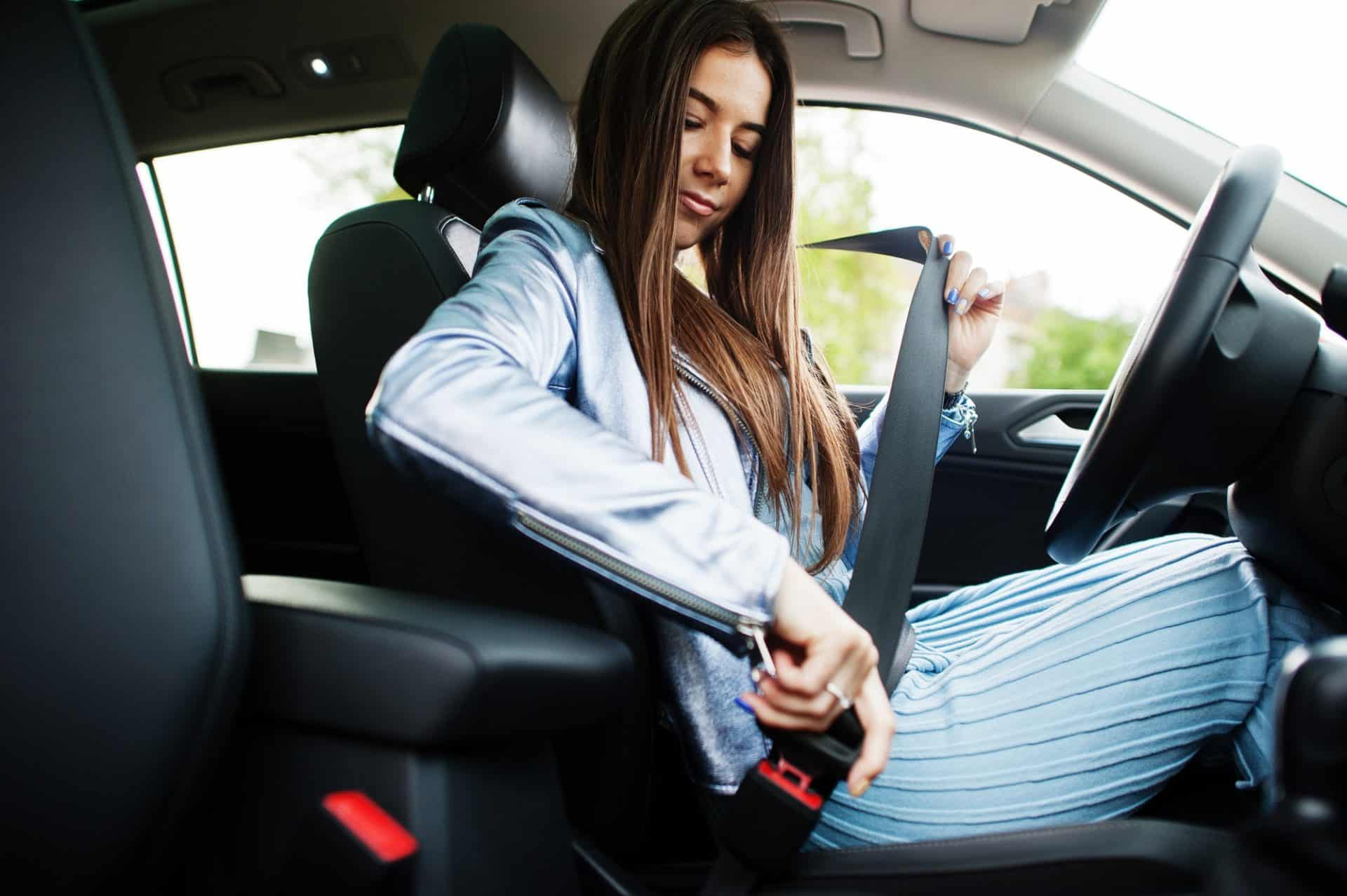 Gorgeous woman sitting inside car interior and tie belt.
